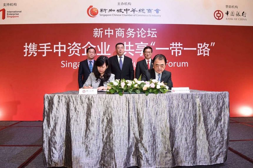 Signing the deal at the Singapore China Business Forum are Ms Wang Yan, deputy general manager of Bank of China Singapore, and Mr Wu Hsioh Kwang, SCCCI vice-president, in the presence of (back row, from left) Bank of China Singapore general manager Q