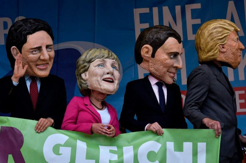 Performers wearing masks of (left to right) Prime Minister of Canada Justin Trudeau, German Chancellor Angela Merkel, French President Emmanuel Macron and US President Donald Trump during a demonstration called by several NGOs ahead of the G20 summit
