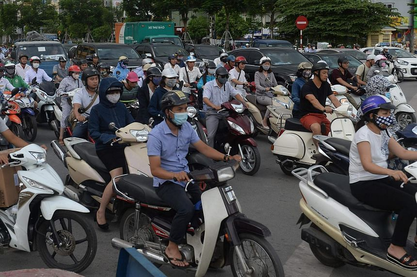 Motorcyclists cross an intersection in downtown Hanoi on July 4, 2017.