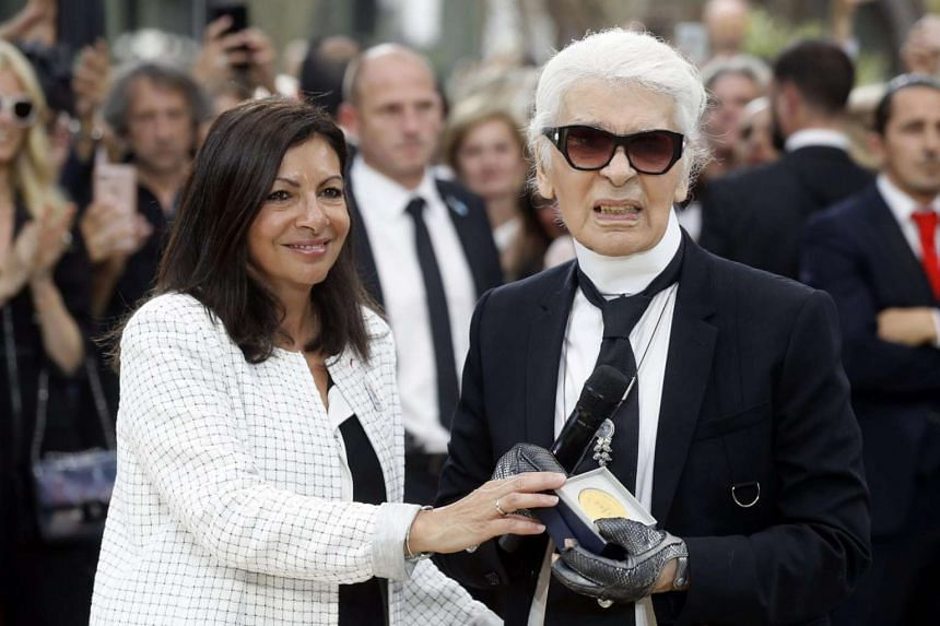 German designer Karl Lagerfeld (right) receives the Paris Grand Vermeil Medal from Paris City Mayor Anne Hidalgo after presenting his Fall/Winter 2017/2018 Haute Couture collection for Chanel, on July 4, 2017.