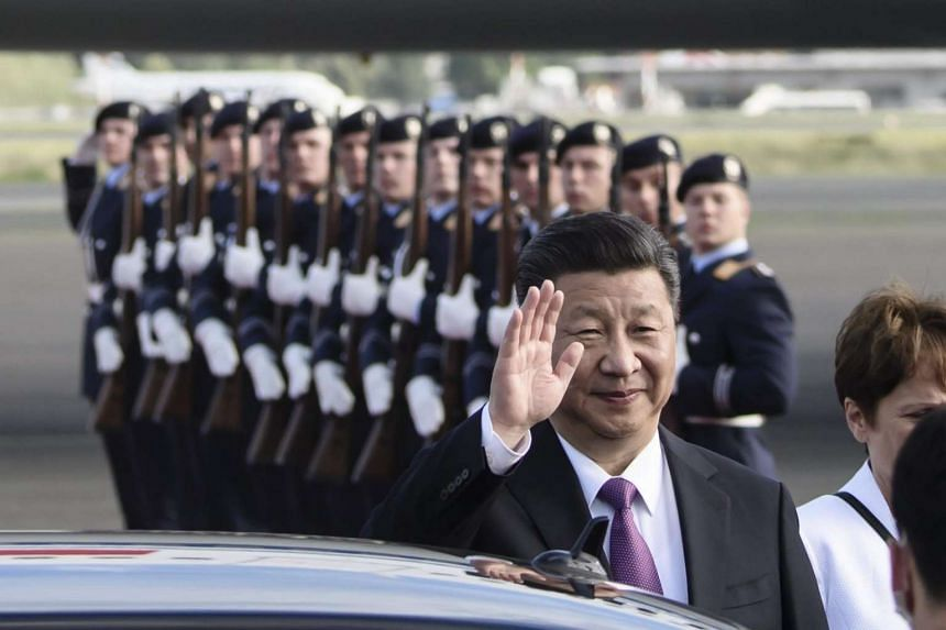 Chinese President Xi Jinping waves after his arrival at the military part of the airport Berlin-Tegel in Berlin, Germany.