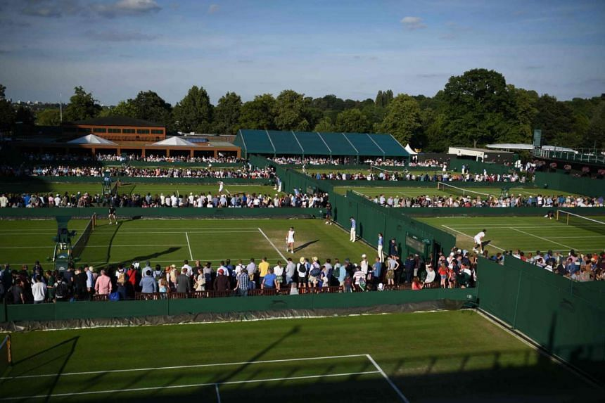 Fans watch the play on outside courts at The All England Lawn Tennis Club in Wimbledon.