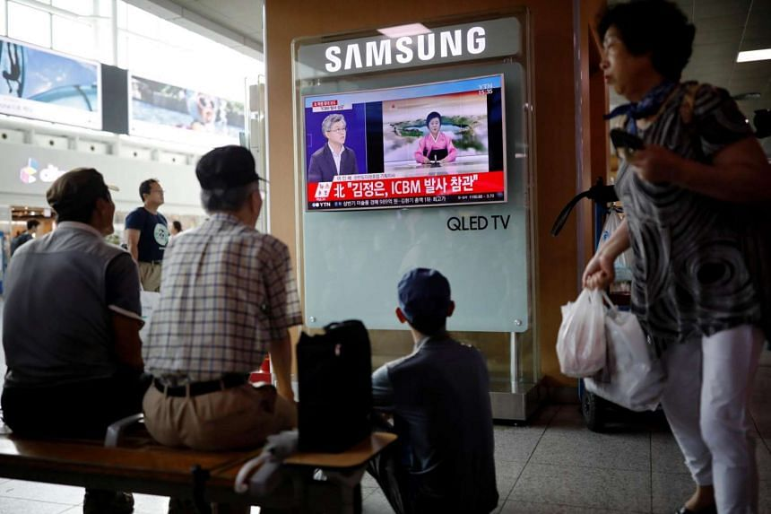 People watching a TV broadcast of a news report on North Korea's Hwasong-14 missile at a railway station in Seoul, South Korea, on July 4, 2017.