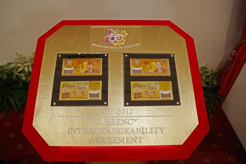 Commemorative fifty-dollar notes from the Brunei (left) and Singapore displayed during a commemorative note presentation ceremony at the Istana Presidential Palace in Singapore on July 5, 2017.