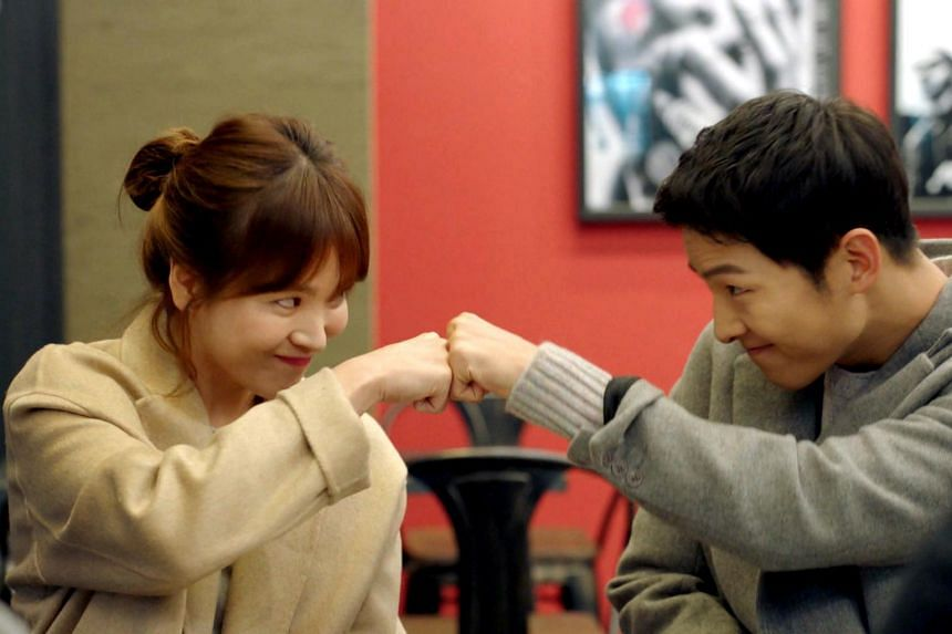 Song Joong Ki (right) and Song Hye Kyo fist bumping as they pose for a photo.