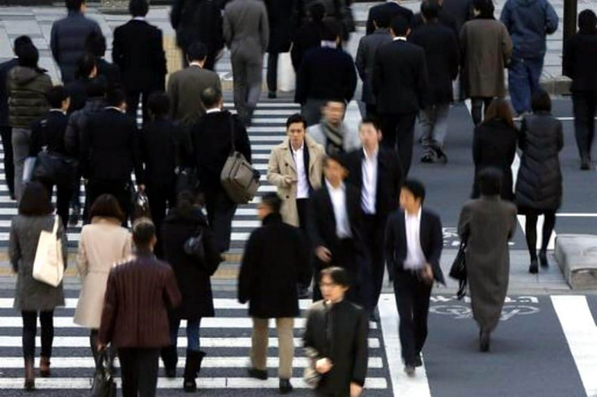 Pedestrians cross a street at a business district in Tokyo on Feb 20, 2013.