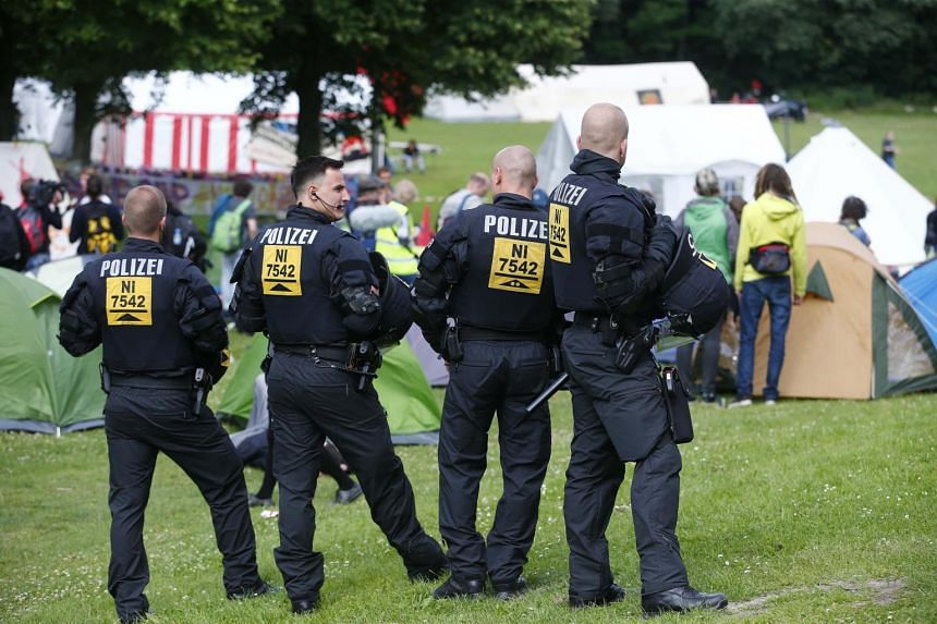 German riot police observe activists from ATTAC organisation setting up a camp as they protest ahead of the upcoming G20 summit in Hamburg.