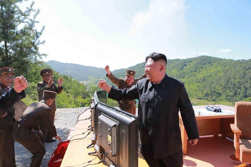 North Korean leader Kim Jong Un (right) reacting after the test-fire of the intercontinental ballistic missile Hwasong-14 at an undisclosed location.