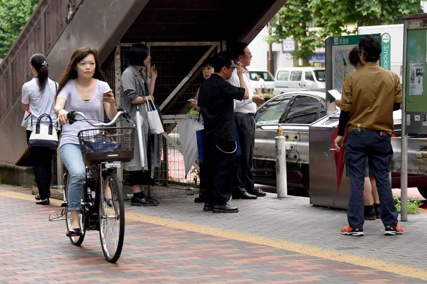 A woman cycles past a smoking corner on the street in Tokyo.