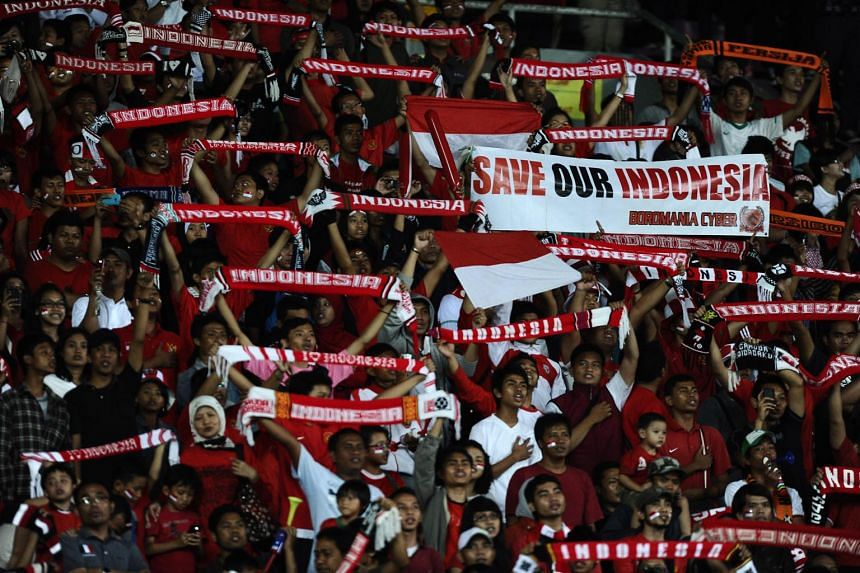 Indonesia fans, decked out in their national colours, cheering and singing before the start of the match between Indonesia and Thailand during the 26th South-east Asian (SEA) Games.