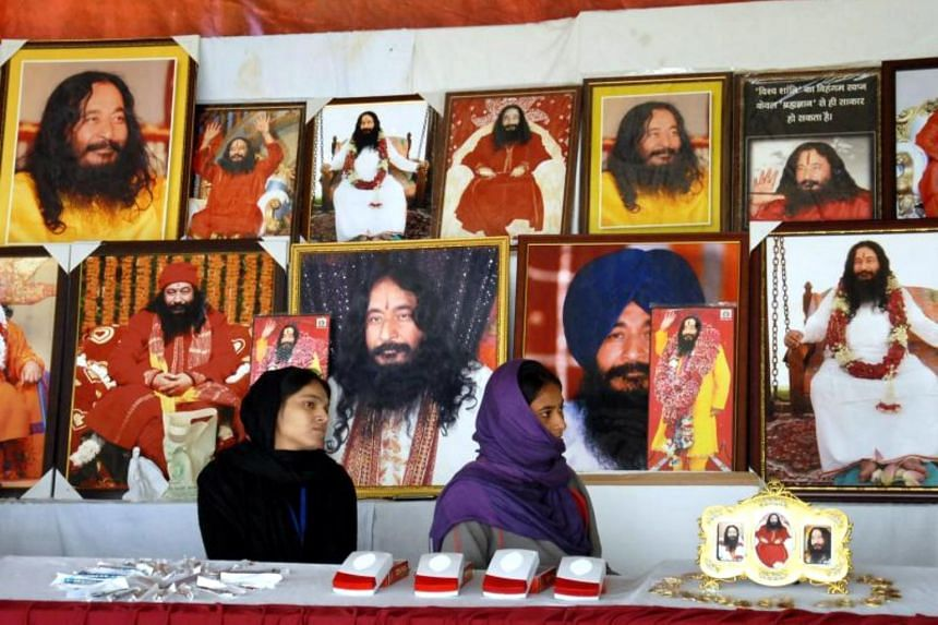 Indian followers of deceased guru Ashutosh Maharaj sitting in front of posters bearing his image at a stall during a congregation at his ashram on Dec 14, 2014.