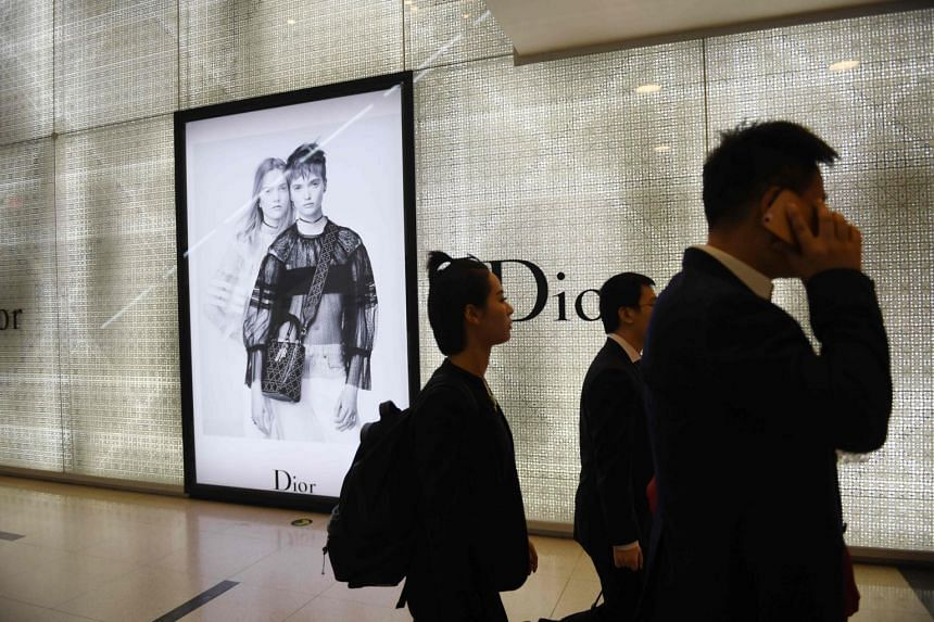 People walk past a luxury store in a shopping mall in Beijing.