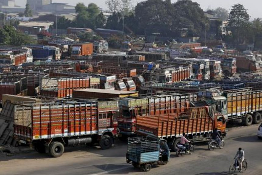Trucks are seen parked in an open plot near a national highway on the outskirts of Ahmedabad, India.