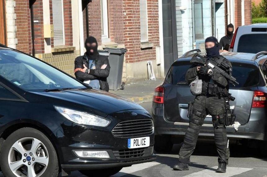 Police officers of an anti-terrorism unit and of French intelligence agency (DGSI) patrol in a street on Wattignies, northern France, after a man was arrested during a French-Belgian anti-terrorist operation on July 5, 2017.