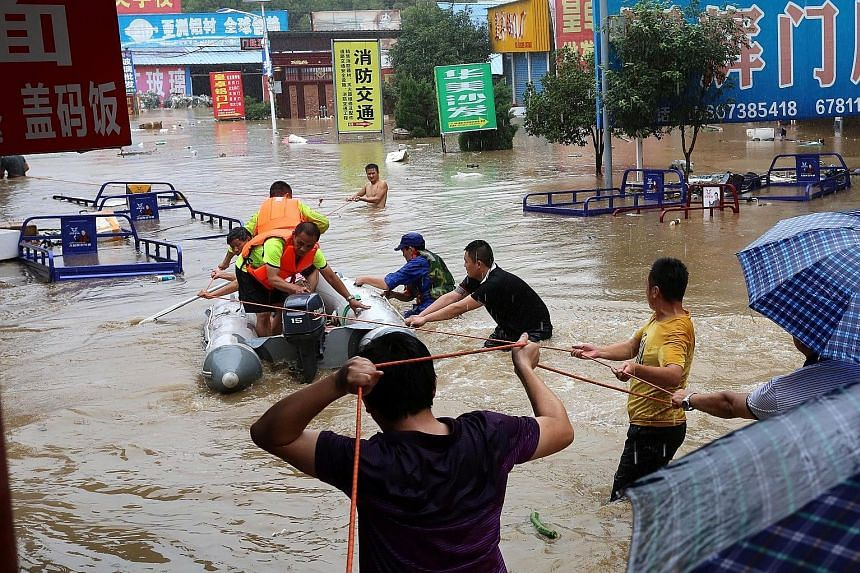 Rescuers evacuating residents from a flooded area in Loudi city, Hunan province, on Saturday. The floods have also delayed grain on barges and damaged farms along the Yangtze River.