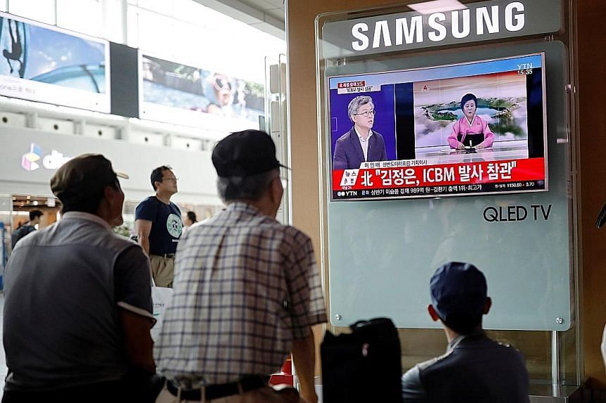 People in Seoul watching a TV broadcast of a news report on North Korea's launch of an intercontinental ballistic missile yesterday.