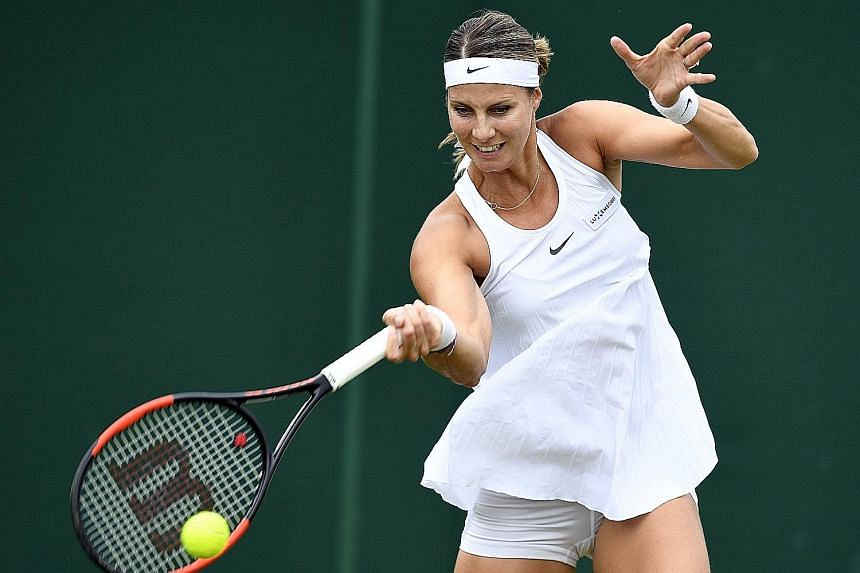 Pregnant Mandy Minella donning a loose-fitting dress during her Wimbledon first-round loss to Francesca Schiavone.