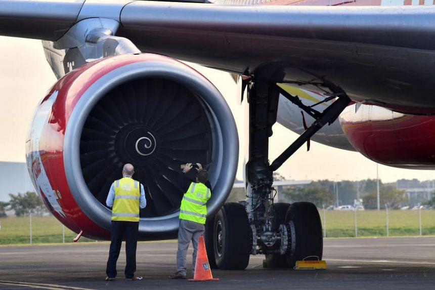 Officials inspect an engine of Malaysian budget carrier AirAsia X Flight D7207 after it was diverted and forced to land because an engine was damaged during take-off by what was thought to be a bird strike at Brisbane Airport in Australia.
