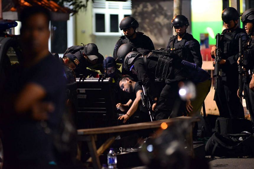Indonesian police investigate the site of an attack after a suspected Islamist militant stabbed two Indonesian police officers after prayers at a mosque near the national police headquarters in Jakarta.