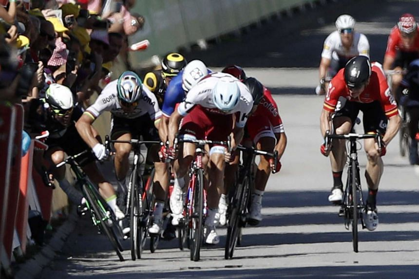 Bora Hansgrohe team rider Peter Sagan of Slovakia elbowing Team Dimension Data rider Mark Cavendish of Britain into the barriers during the final sprint in the fourth stage of the 104th edition of the Tour de France cycling race on July 4, 2017.