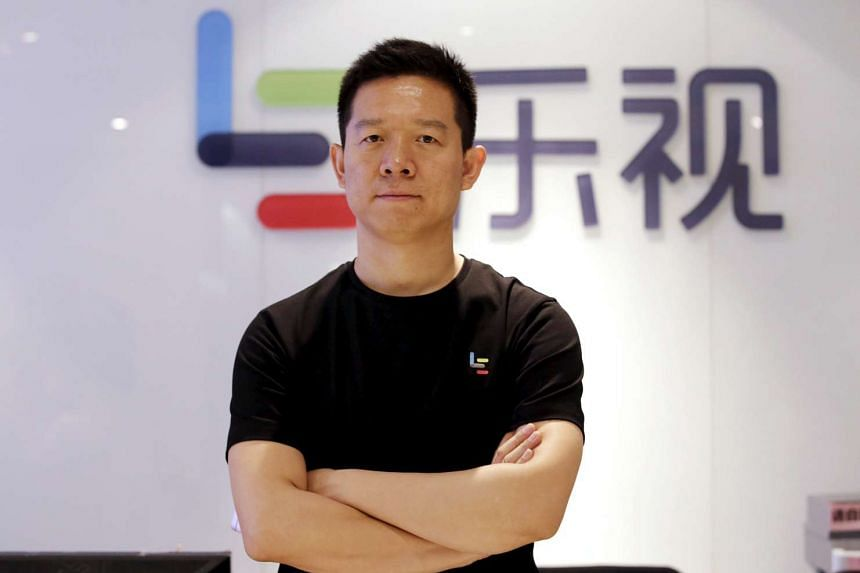 Jia Yueting, co-founder and head of Le Holdings Co Ltd, also known as LeEco and formerly as LeTV, poses for a photo in front of a logo of his company.