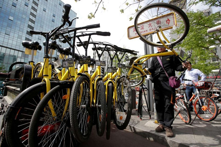 A staff member from the bike-sharing company Ofo gathers its shared bikes for use during the evening rush hour, in Beijing.