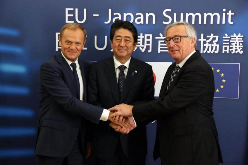 Japan's Prime minister Shinzo Abe (centre) is welcomed by European Council President Donald Tusk (left) and EU Commission President Jean-Claude Juncker prior to a EU Japan leaders summit meeting in Brussels, Belgium, on July 6, 2017.