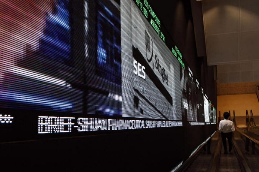 A man walking down the escalator next to the big screen at the Singapore Exchange (SGX).