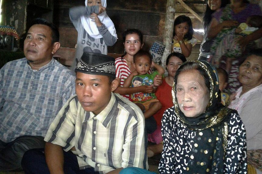 Rohaya Binti Kiagus Muhammad Jakfar (second from right), 73, sitting with her 15-year-old teenage husband Selamet Riyadi (second from left) in Baturaja, South Sumatra province.