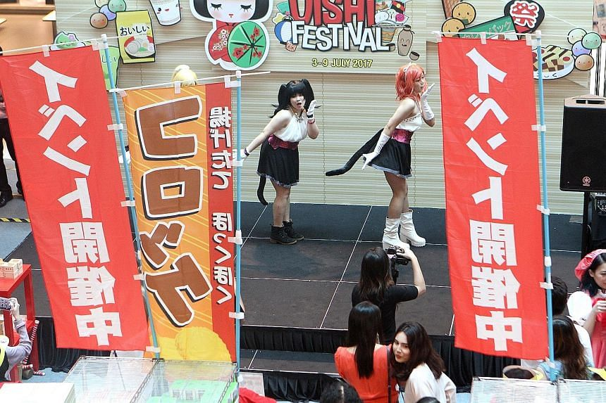 Cosplayers performing at the Cold Storage Oishi Festival Atrium Fair at Plaza Singapura yesterday. Among the food offerings at the fair were crispy croquettes and beef rice bowls, as well as Hokkaido cheesecakes and lavender ice cream. The festival w