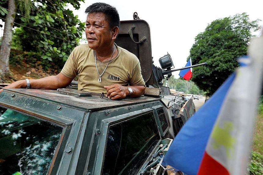 """Above: Among the three people arrested yesterday was Monaliza Romato, who reportedly replaced her aunt, Ominta Maute, as """"matriarch"""" of the group that attacked Marawi. Right: A Filipino army driver of an armoured vehicle on the route to Marawi, where"""