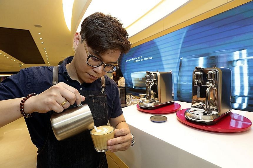 Founder of mobile coffee catering service Kinsmen Coffee Jervis Tan creating latte art at the media launch of the Nespresso boutique in Ion Orchard on Tuesday.