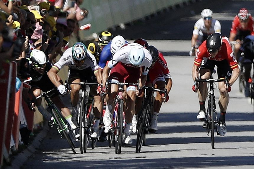 Astana rider Fabio Aru of Italy powering home to win the Tour de France fifth stage. Below: Bora-Hansgrohe cyclist Peter Sagan catching Dimension Data's Mark Cavendish with a stray elbow during the final sprint of the fourth stage. The resultant cras