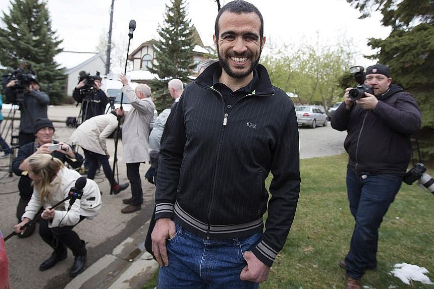 Mr Omar Khadr leaving a news conference after being released on bail in Edmonton, Alberta, in May 2015. Mr Khadr, a Canadian, was captured in Afghanistan in 2002 at age 15 and was the youngest prisoner at Guantanamo Bay.
