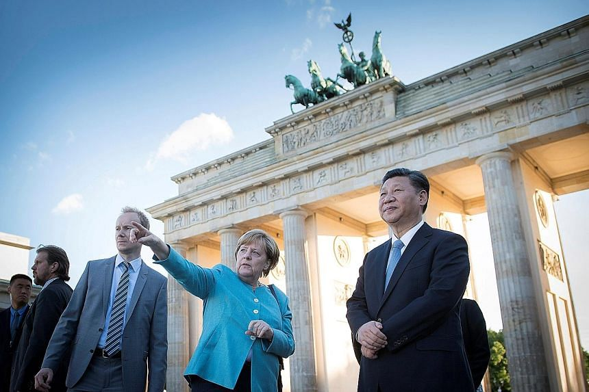 """German Chancellor Angela Merkel and Chinese President Xi Jinping in front of the Brandenburg Gate in Berlin yesterday. Mr Xi, who visited the German capital two days ahead of the G-20 summit in Hamburg, said: """"German-Chinese relations stand before a"""