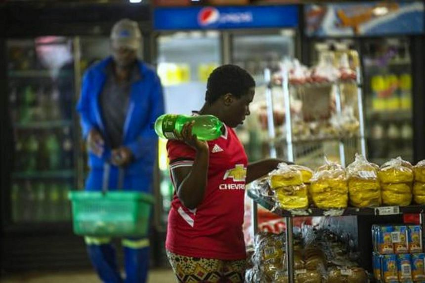 A woman holding a bottle of soft drink as she shops around at a local supermarket in the Township of Zandspruit, Greater Johannesburg, South Africa.