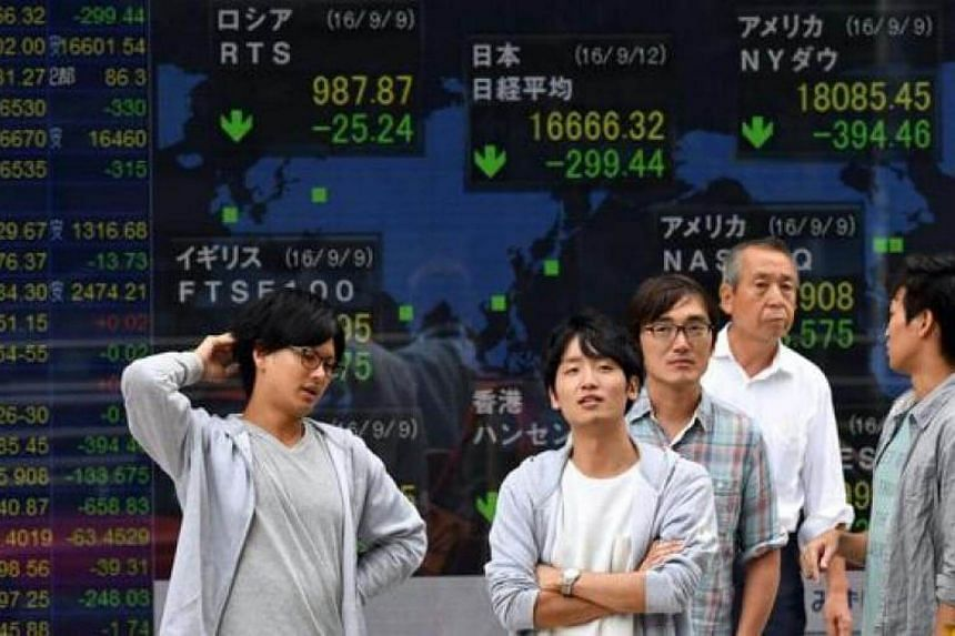 Pedestrians stand in front of a monitor displaying stock markets index in Tokyo.