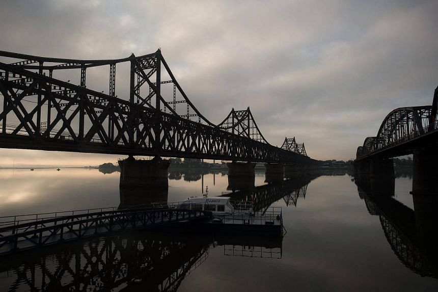 The sun rises over the Friendship bridge on the Yalu River connecting the North Korean town of Sinuiju and Dandong.