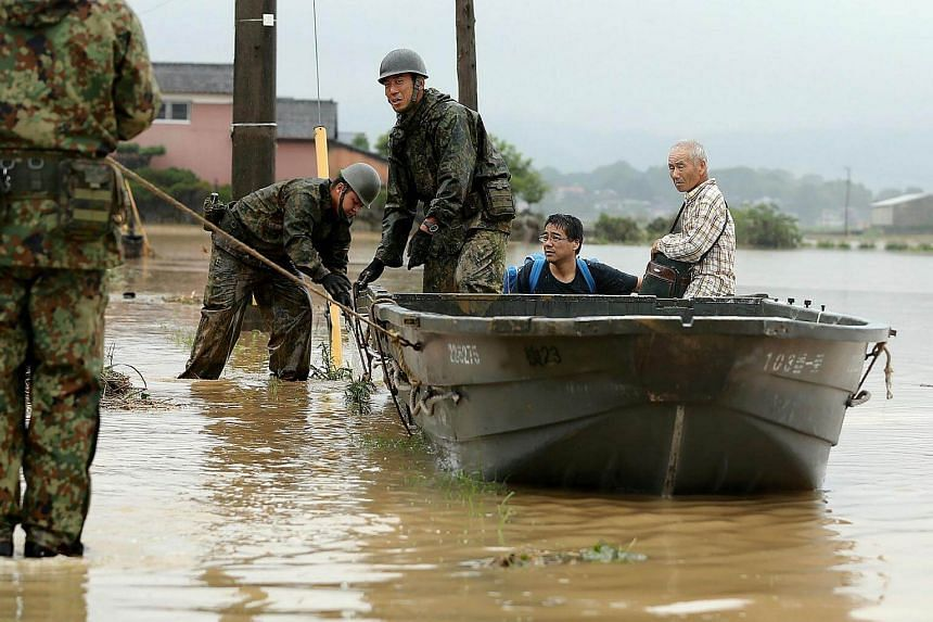 Japanese soldiers help local residents evacuate from flooded area in Asakura, Fukuoka prefecture, on July 6, 2017.