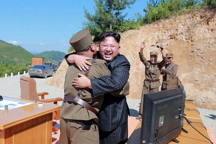 North Korean leader Kim Jong Un (centre) celebrating the successful test-fire of the intercontinental ballistic missile Hwasong-14 at an undisclosed location.