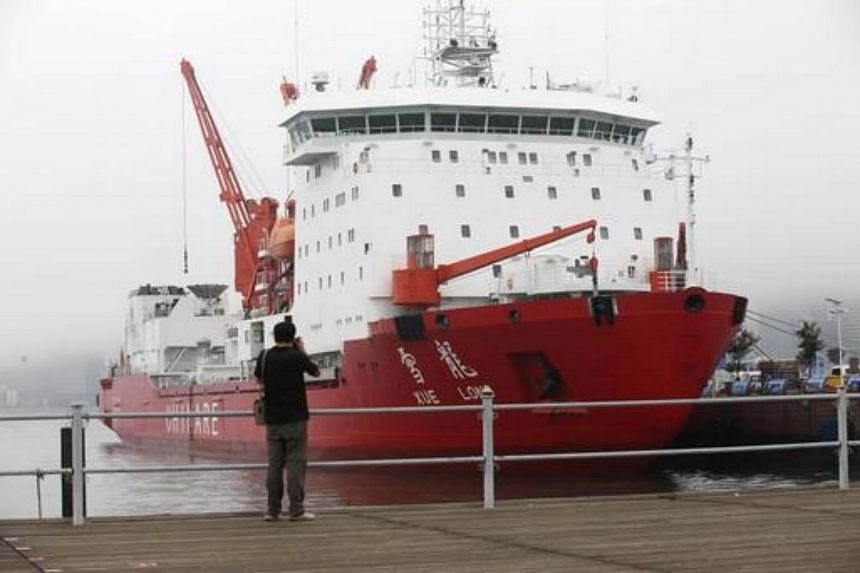 A man taking a photo of Chinese icebreaker Xuelong.