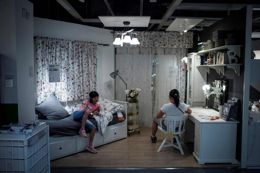 This picture taken on July 5, 2017, shows a mother with her child escaping the summer heat by relaxing on a bed in a Ikea store in downtown Shanghai.
