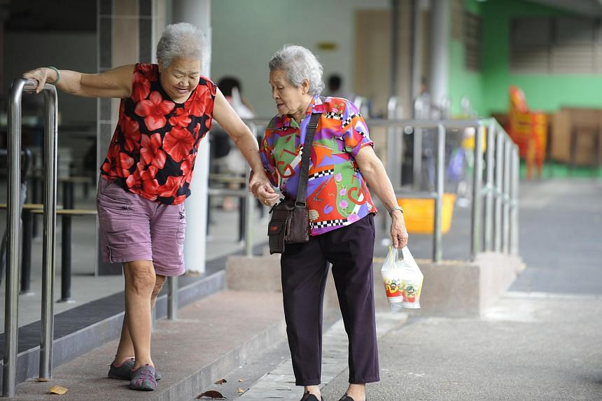 Two elderly women holding hands while negotiating some steps at a hawker centre in Toa Payoh Lorong 8.