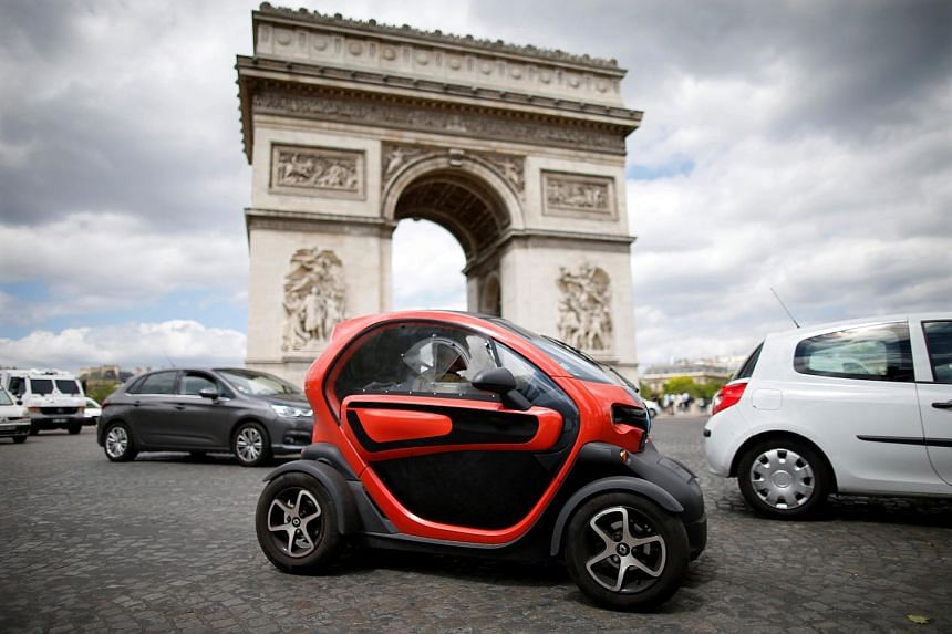 A Twizy electric car by French car manufacturer Renault, drives past the Arc de Triomphe in Paris, France, May 30, 2017.