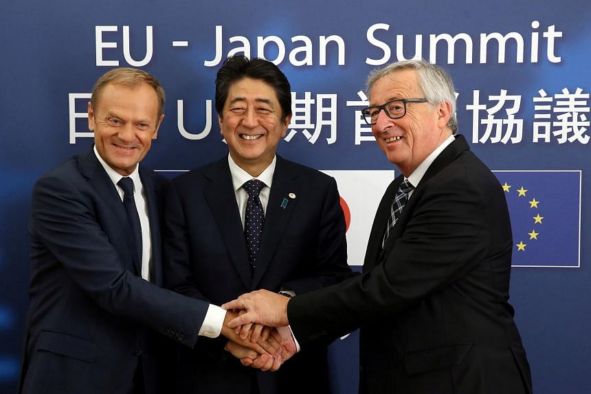 Japan's Prime Minister Shinzo Abe (centre) is welcomed by European Council President Donald Tusk (left) and European Commission President Jean-Claude Juncker at the start of a EU-Japan summit in Brussels, Belgium on July 6, 2017.