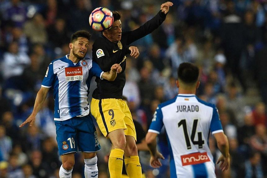 Atletico Madrid's forward Fernando Torres beating Espanyol's Argentinian forward Pablo Piatti to the ball during their Spanish league football match at the RCDE Stadium in Cornella de Llobregat on April 22, 2017.