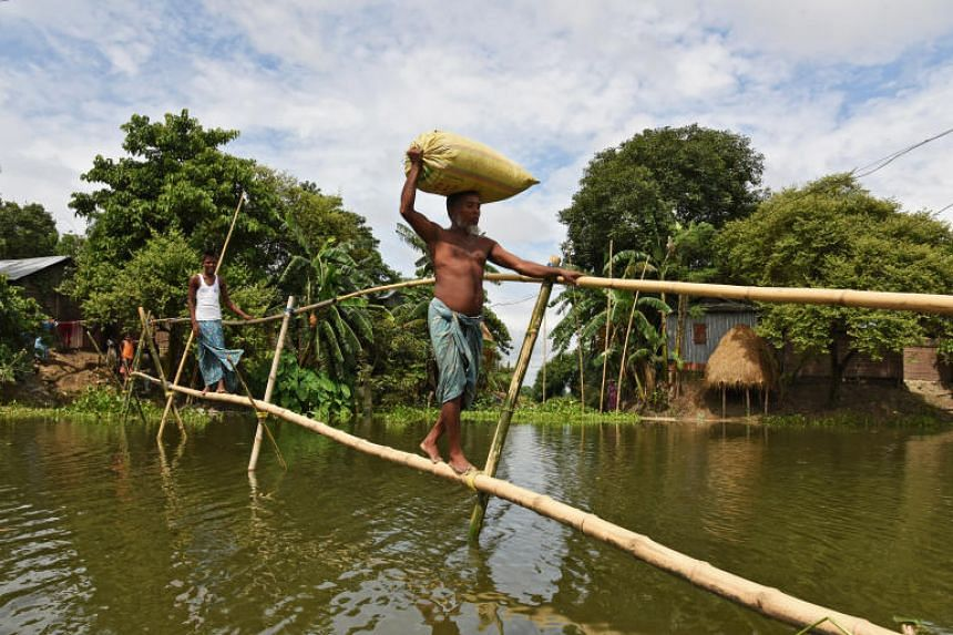 Villagers use a makeshift bamboo bridge to move across flooded areas of Morigaon district in Assam.