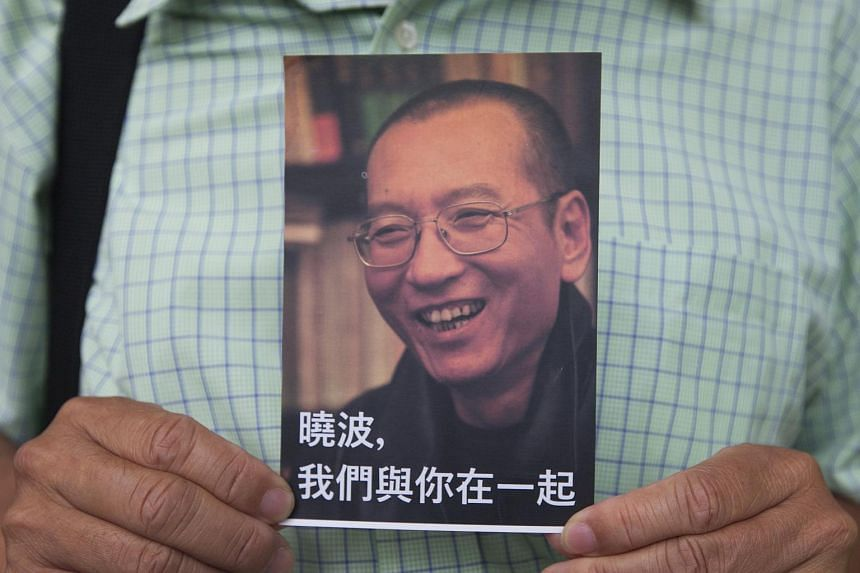 An activist holds up one of the postcards containing messages of support to be sent to Chinese dissident Liu Xiaobo in Hong Kong, China on 5 July 2017.