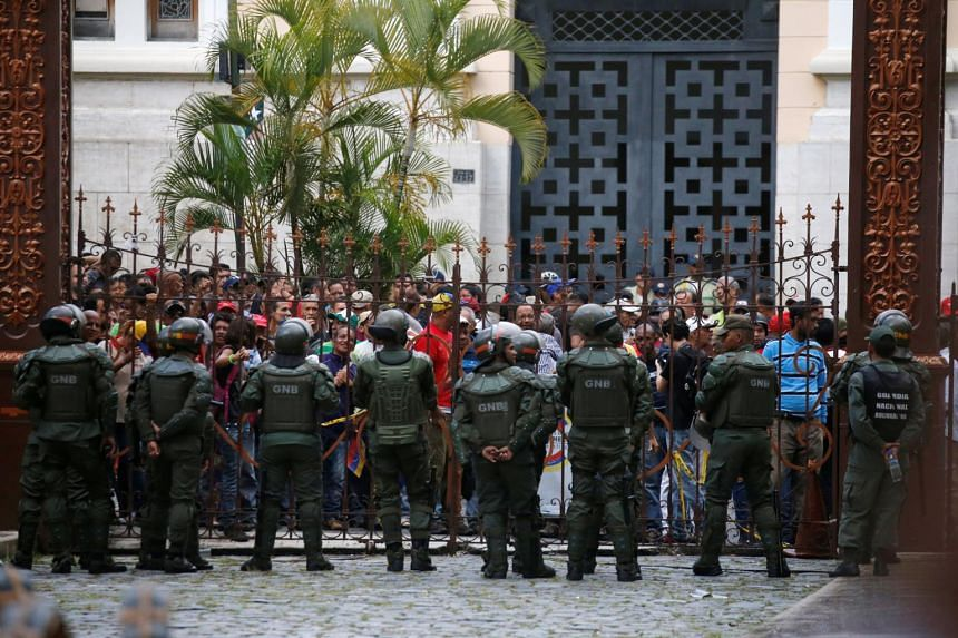Government supporters stand outside the gates of the National Assembly as they besiege the building, preventing people on the inside from leaving, in Caracas, Venezuela, on July 5, 2017.