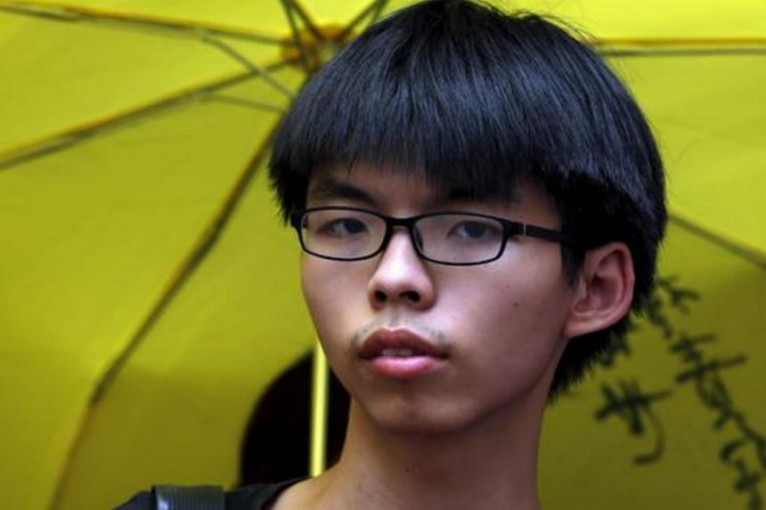 Student leader Joshua Wong stands in front of a supporter holding a yellow umbrella, symbol of the Occupy Central movement, outside a police station in Hong Kong, on July 14, 2015.